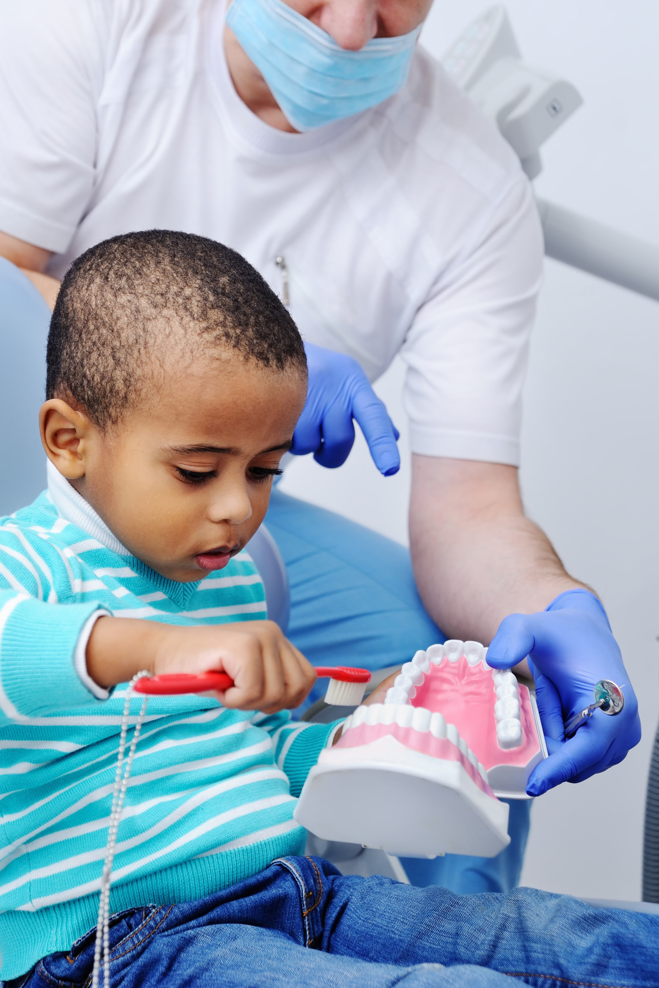 Pediatric dentist shows young child how to brush their teeth on an enlarged tooth model