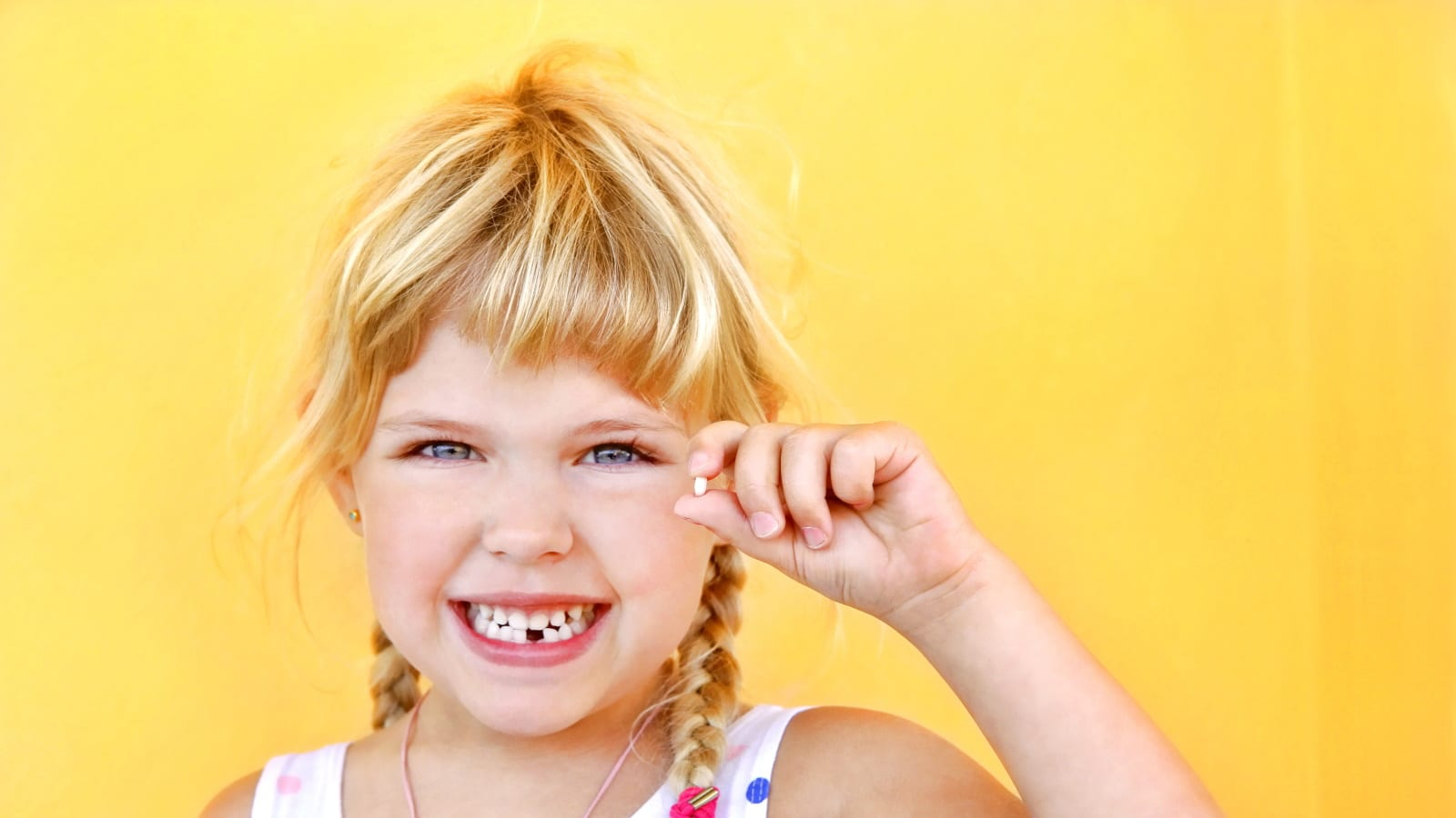Child holding a baby tooth