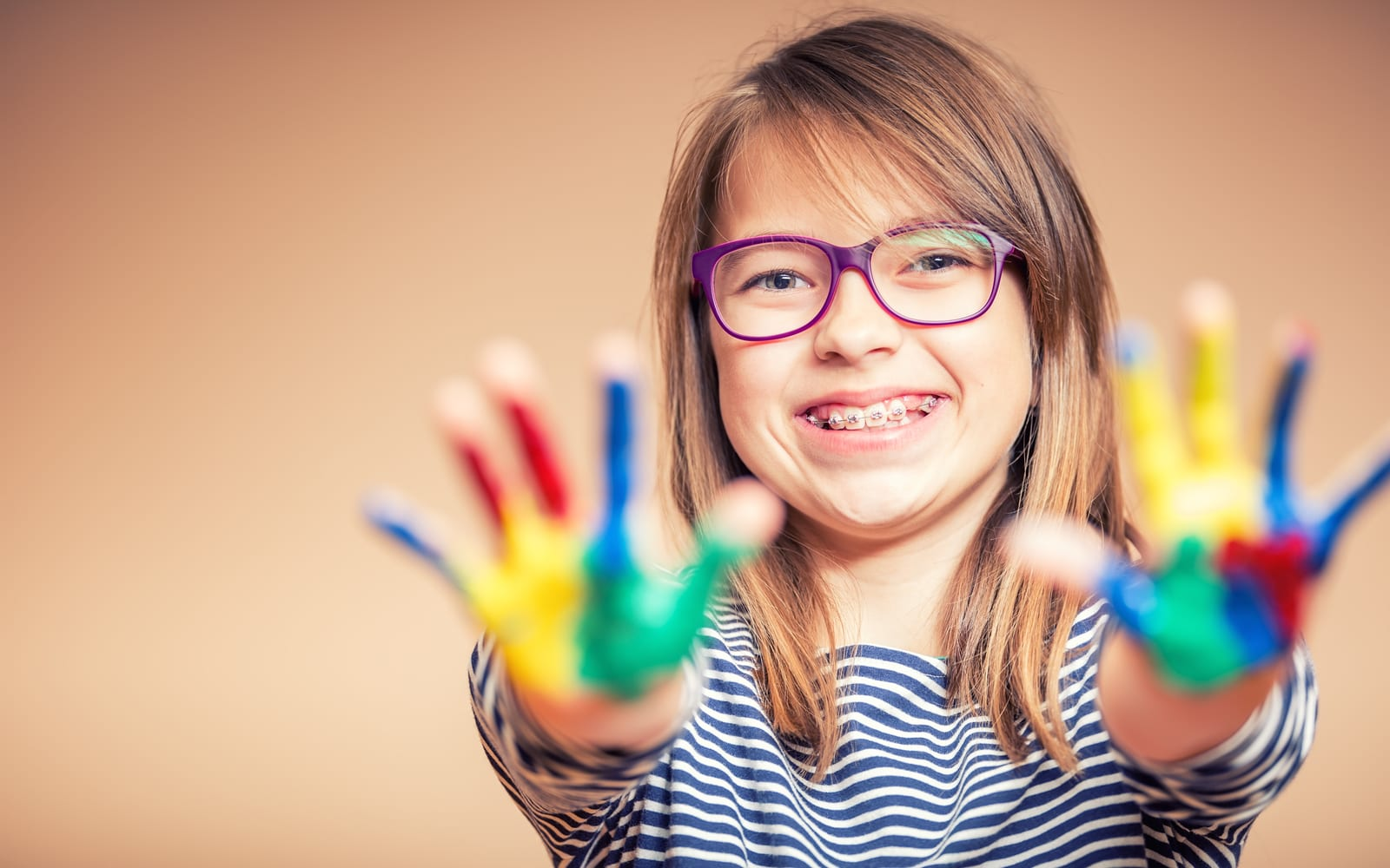 Child with braces and colored paint on hands